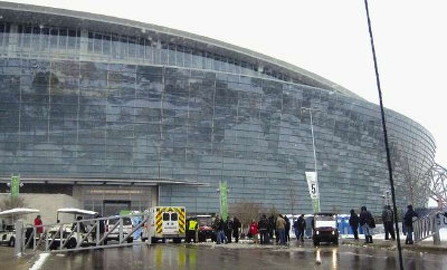 Medical personnel tend to a person injured by falling ice off of Cowboys Stadium, the site of Super Bowl XLV in Arlington. An official said that five people were hurt, one critically, by ice falling off the roof on Friday. / AP2011