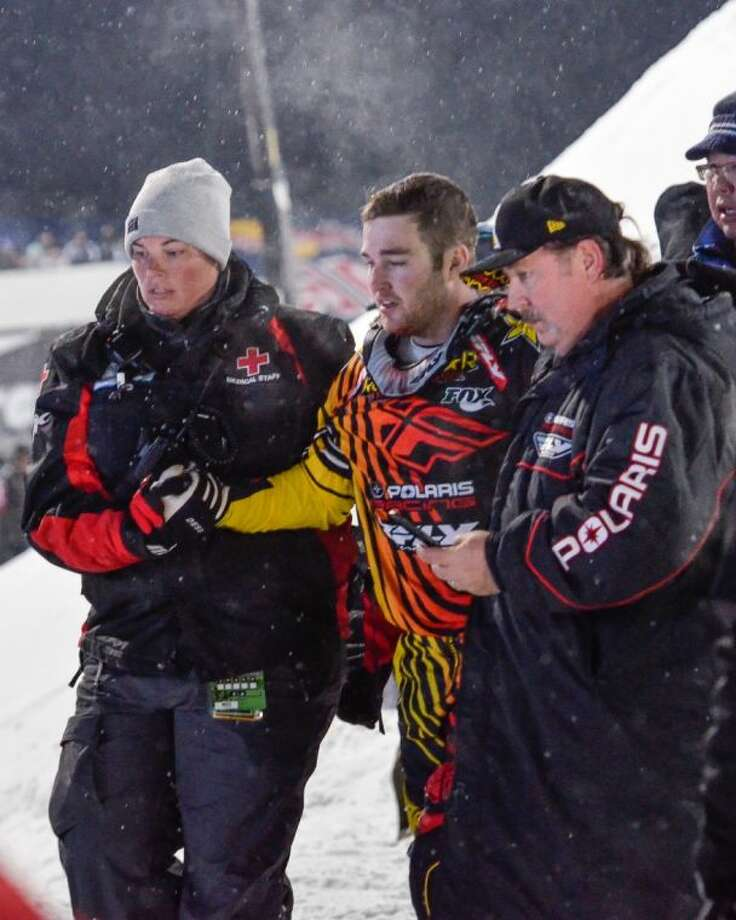 Caleb Moore is helped off the snow following his crash during the ESPN Winter X Games snowmobile freestyle competition Jan. 24 in Aspen, Colo. Photo: Chris Council