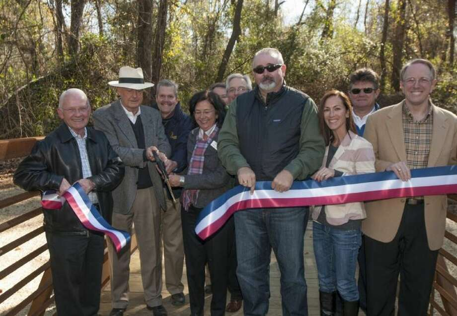 Pictured at the ribbon cutting ceremony for The George Mitchell Nature Preserve Pedestrian Bridge Ribbon are from left to right: Ed Chance, retired Montgomery County Commissioner Precinct 3; Alex Sutton, Co-President of TWDC; Bob Bruce, Director of Landscape Architecture for TWDC; Amy Lecocq, President of the Indian Springs Village Association; John Powers, Assistant General Manager of The Woodlands Township; Dan Kolkhorst, Vice President, Engineering and Construction for TWDC; Jack Cagle, Harris County Commissioner Precinct 4; Nancy Decker Lent, President of the Creekside Park Village Association; Dennis Johnston, Director of Parks, Harris County Precinct 4; and Robert Collins, former Special Counsel, Montgomery County Precinct 3. Photo: Ted Washington