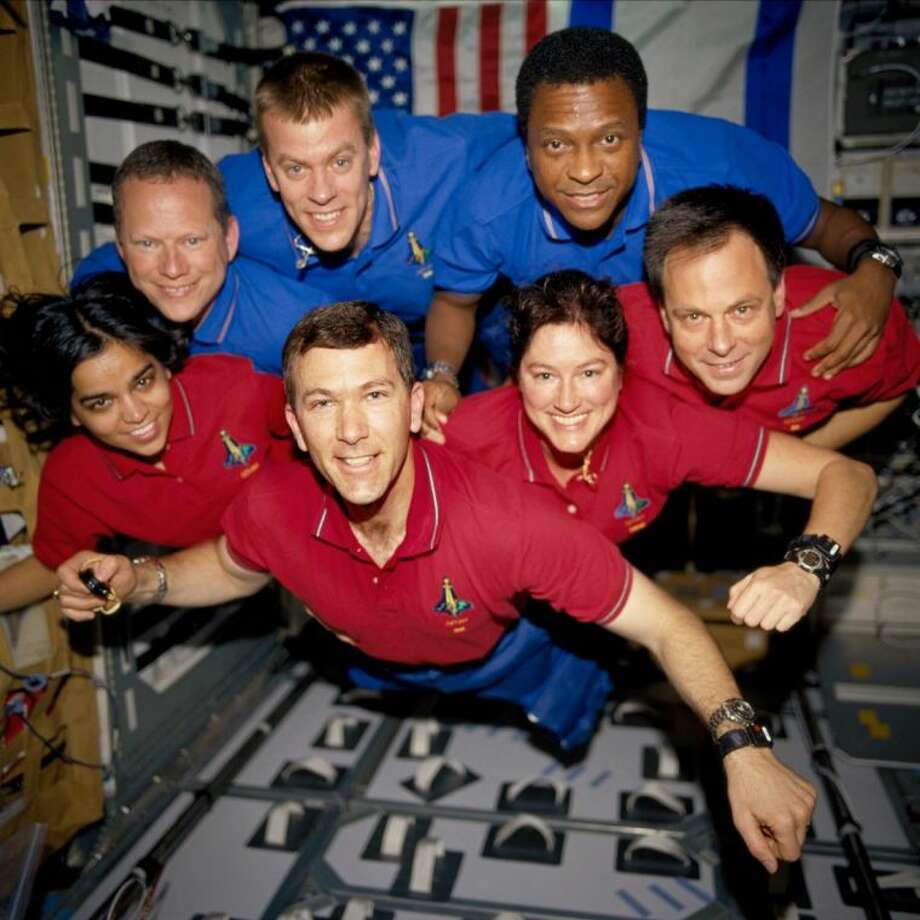 This photo provided by NASA in June 2003 shows STS-107 crew members in the SPACEHAB Research Double Module (RDM) aboard the Space Shuttle Columbia. On Feb. 1, 2003, the seven crew members were lost as the Columbia fell apart over East Texas. This picture was on a roll of unprocessed film later recovered by searchers from the debris. From the left (bottom row), wearing red shirts to signify their shift's color, are astronauts Kalpana Chawla, mission specialist; Rick D. Husband, mission commander; Laurel B. Clark, mission specialist; and Ilan Ramon, payload specialist. From the left (top row), wearing blue shirts, are astronauts David M. Brown, mission specialist; William C. McCool, pilot; and Michael P. Anderson, payload commander. Photo: HOPD