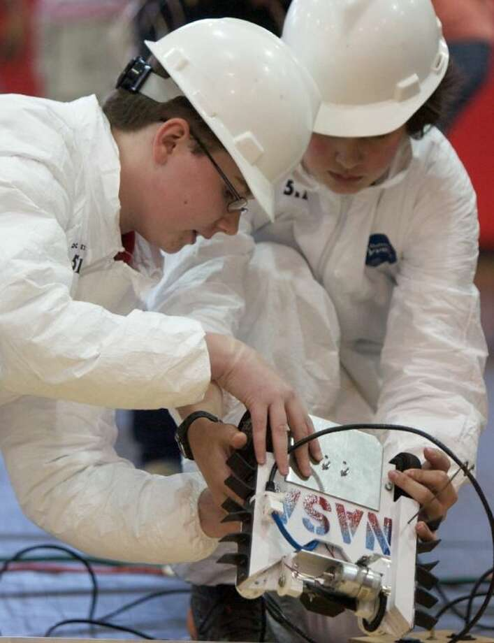 "Nick Roush and Samuel Evans, members of the ""Brain Stormers"" team, prepare their robot before competing in Saturday's SCI://TECH Engineering Design Competition held at Moorhead Jr. High. Photo: Staff Photo By Eric Swist"