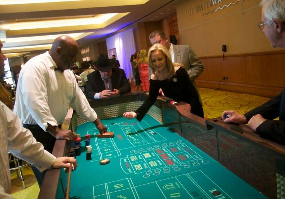 A woman rolls the dice on the craps table during the 18th Annual CASA Gala at The Woodlands Waterway Marriott Hotel & Convention Center on Saturday evening. Photo: Staff Photo By Eric Swist