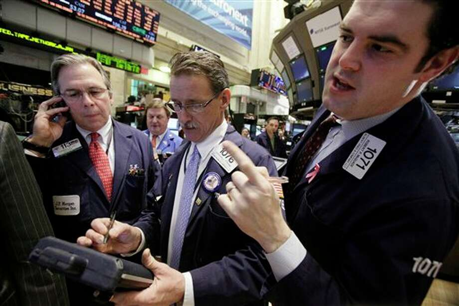In this Jan. 25, 2012 photo, traders Thomas Kay, left, Marshall Ryan, center, and Robert McQuade work on the floor of the New York Stock Exchange. World stock markets rose on Thursday, Jan. 26, after the U.S. Federal Reserve pledged to keep interest rates low until late 2014 to nurture the country's stubbornly slow economic recovery. (AP Photo/Richard Drew) Photo: Richard Drew / AP