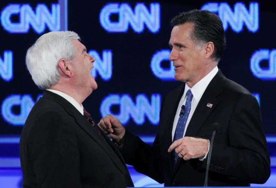 Republican presidential candidates, former House Speaker Newt Gingrich and former Massachusetts Gov. Mitt Romney, talk during a commercial break at the Republican presidential candidates debate in Jacksonville, Fla., Thursday. Photo: Matt Rourke