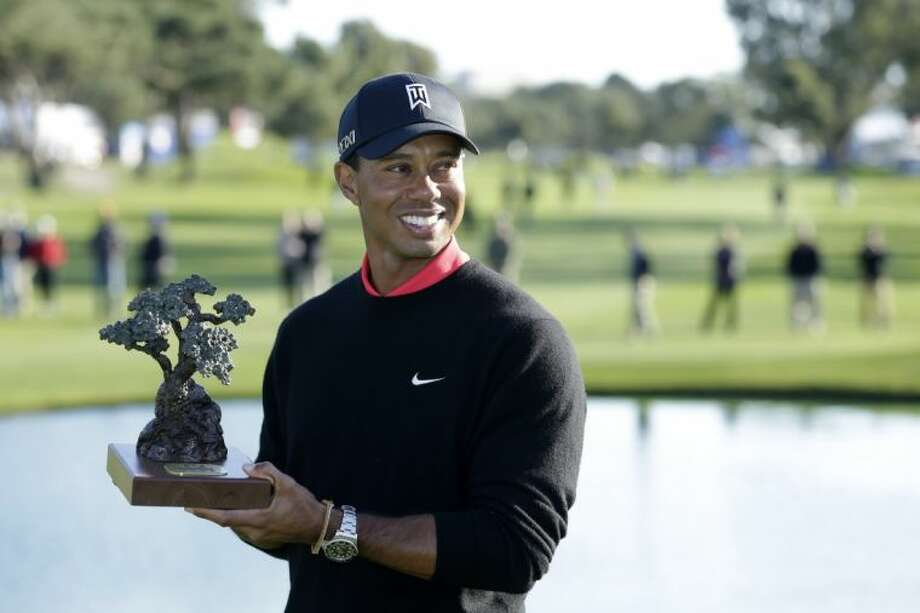Tiger Woods holds up the trophy after winning the Farmers Insurance Open golf tournament at the Torrey Pines Golf Course. It's Woods' seventh victory in the event. Photo: Gregory Bull