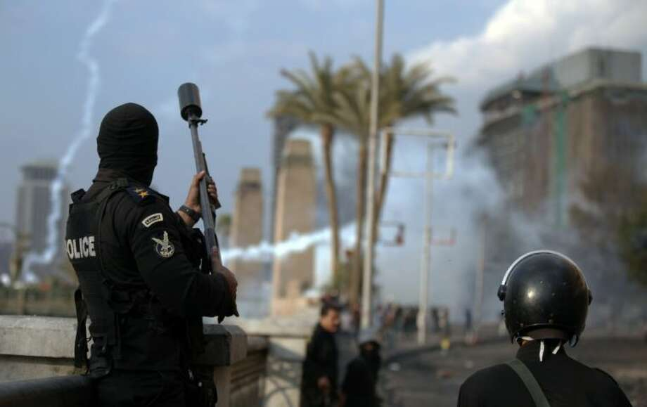 An Egyptian police officer fires tear gas at protesters during clashes near Tahrir Square, Cairo, Egypt, Tuesday, Jan. 29, 2013. Intense fighting for days around central Tahrir Square engulfed two landmark hotels and forced the U.S. Embassy to suspend public services on Tuesday. Photo: Khalil Hamra