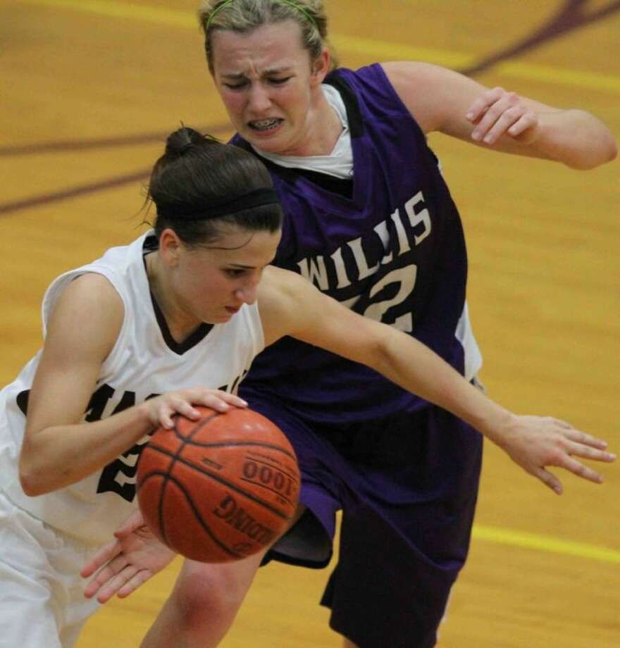 Magnolia guard Tori Frederick drives past Willis post Haley Sellers during Friday's game at Magnolia High School. To see or purchase this photo and others like it, visit HCNpics.com. Photo: Jason Fochtman