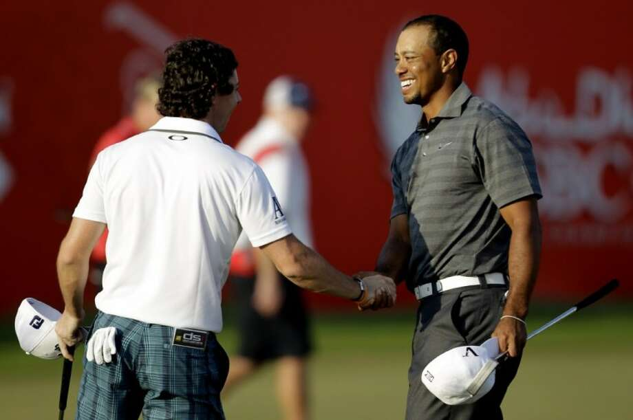 Tiger Woods, shakes hands with Rory McIlroy on the 18th hole after they finished the third round of Abu Dhabi HSBC Championship, Saturday, in Abu Dhabi, United Arab Emirates. Photo: Kamran Jebreili