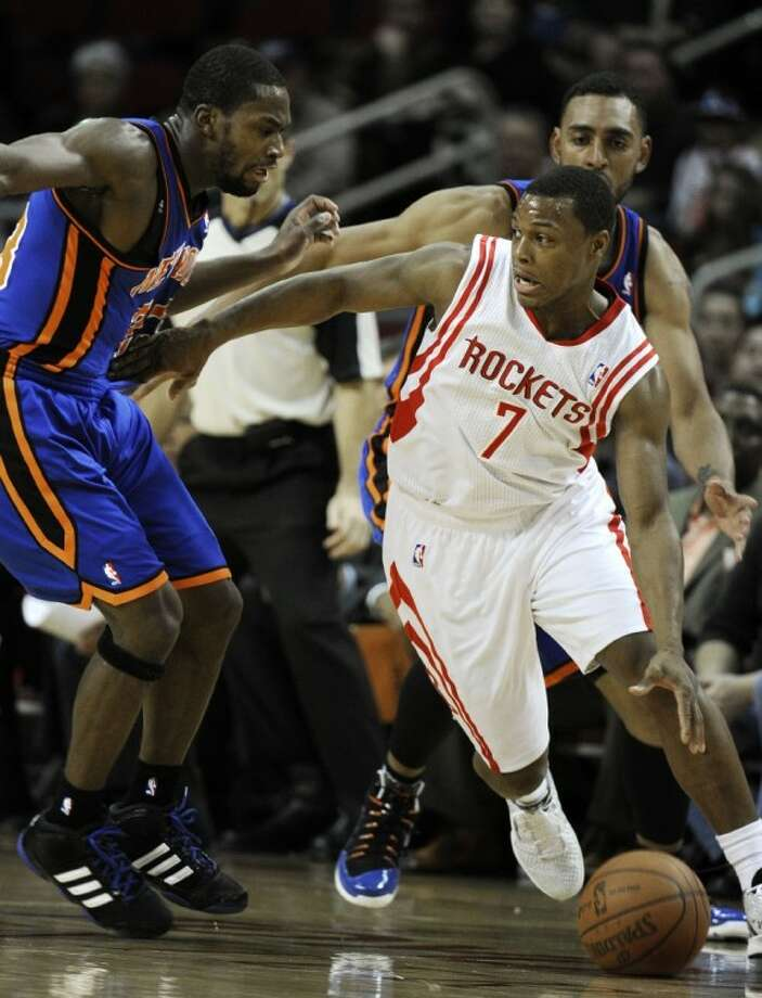 Houston Rockets' Kyle Lowry tries to drive the ball around New York Knicks defenders Toney Douglas and Jared Jeffries, right, in the first half on Saturday in Houston. Photo: Pat Sullivan