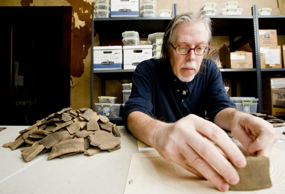 In this Jan. 23, 2013 photo, Tribal Architectural Consultant Tim Perttula takes notes and writes descriptions of the shards of Caddo Indian pottery in the Buddy Calvin Jones Caddo Indian Collection, at the Gregg County Historical Museum in Longview, Texas. One of the largest known collections of Caddo Indian artifacts is being analyzed by new 3-D imaging technology at the Gregg County Historical Museum, as archeologists try to gain new insights into the lives of the ancient East Texas tribe. Zac Selden, a Ph.D. candidate at Texas A&M University, is part of the group working to sort and catalog the artifacts that date back to 1700 A.D. Photo: Michael Cavazos