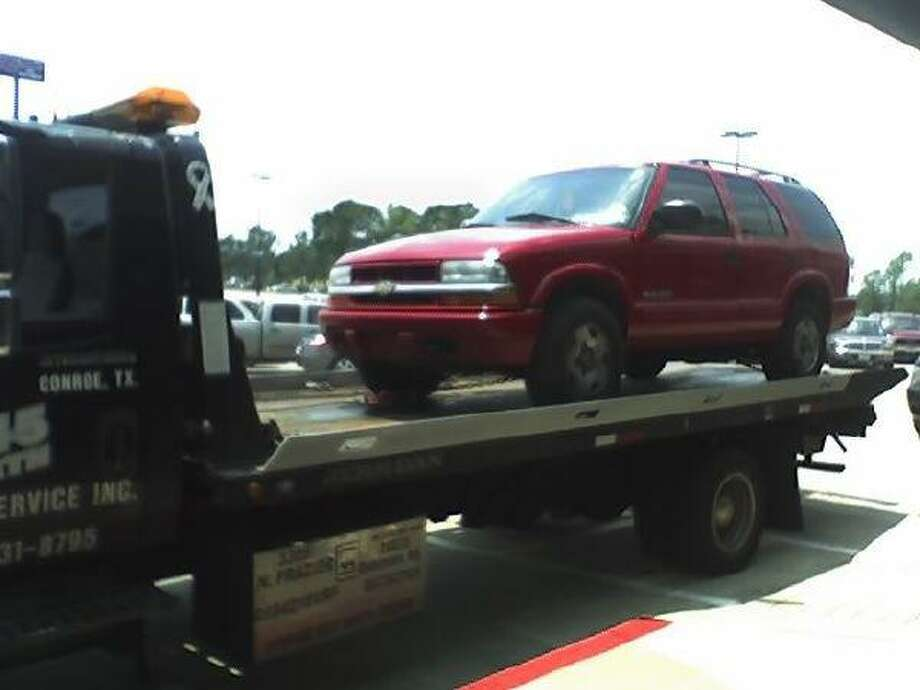 A tow truck hauls away a red Chevrolet SUV allegedly used by three men to flee following the robbery of the Conroe Diamond Exchange jewelry store Tuesday.