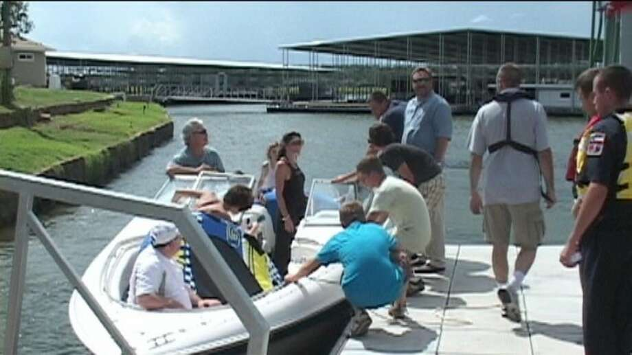 Officials speak with a group of boaters who discovered a woman struggling to stay afloat in Lake Conroe Wednesday afternoon after she was reported missing by her husband.