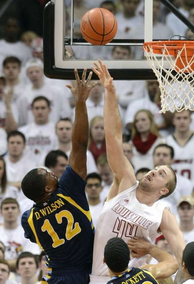 Louisville's Stephan Van Treese, right, jumps to block the shot of Marquette's Derrick Wilson during the second half of their NCAA college basketball game on Sunday, Feb. 3, 2013, in Louisville, Ky. Louisville defeated Marquette 70-51. (AP Photo/Timothy D. Easley) Photo: Timothy D. Easley