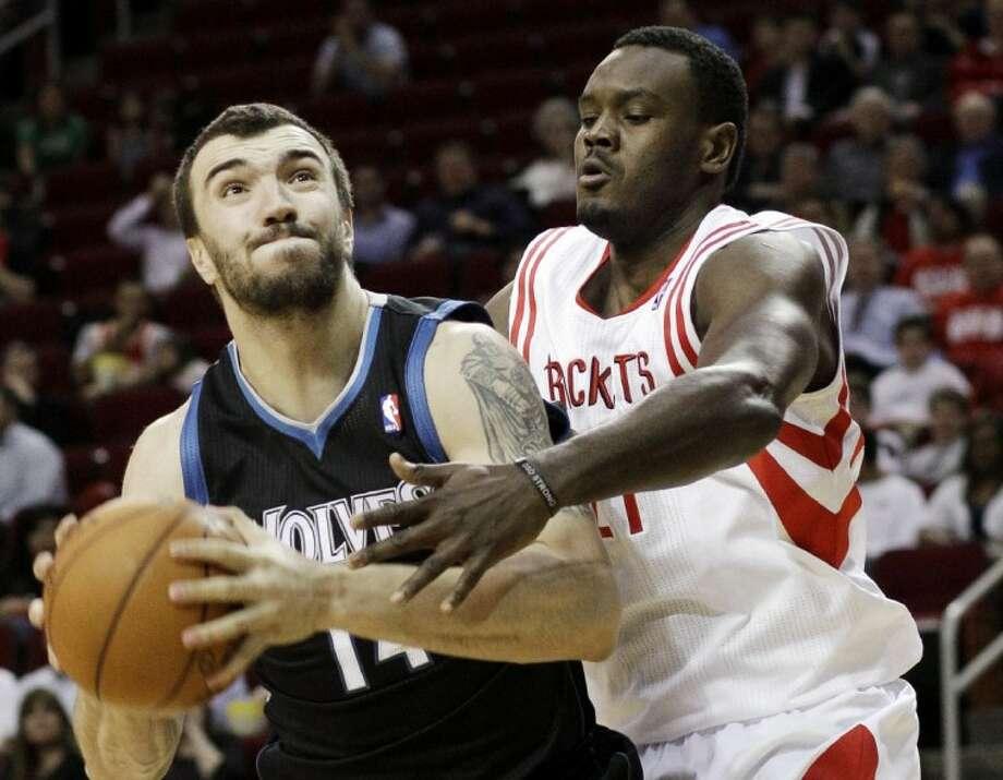 Houston Rockets' Samuel Dalembert pressures Minnesota Timberwolves' Nikola Pekovic in the first half Monday in Houston. Photo: Pat Sullivan