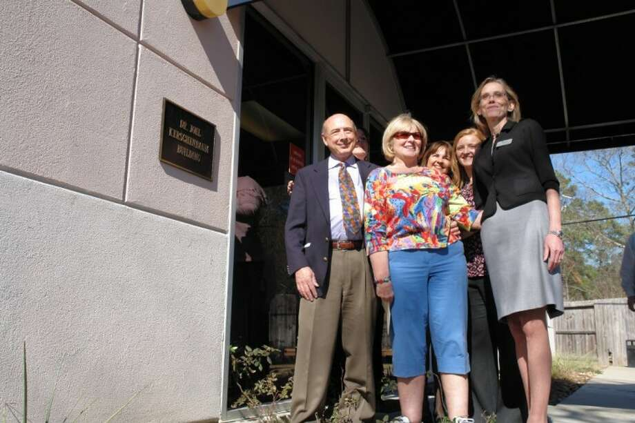 Dr. Joel Kerschenbaum, left, and clinic physician Dr. Janet Roberts, right, pose with clinic staff Sunday afternoon at an event naming the Interfaith Community Clinic building the Dr. Joel Kerschenbaum Building. Kerschenbaum founded the clinic in 1996. The plaque bearing the physician's name was unveiled just outside the clinic's entrance (far left).