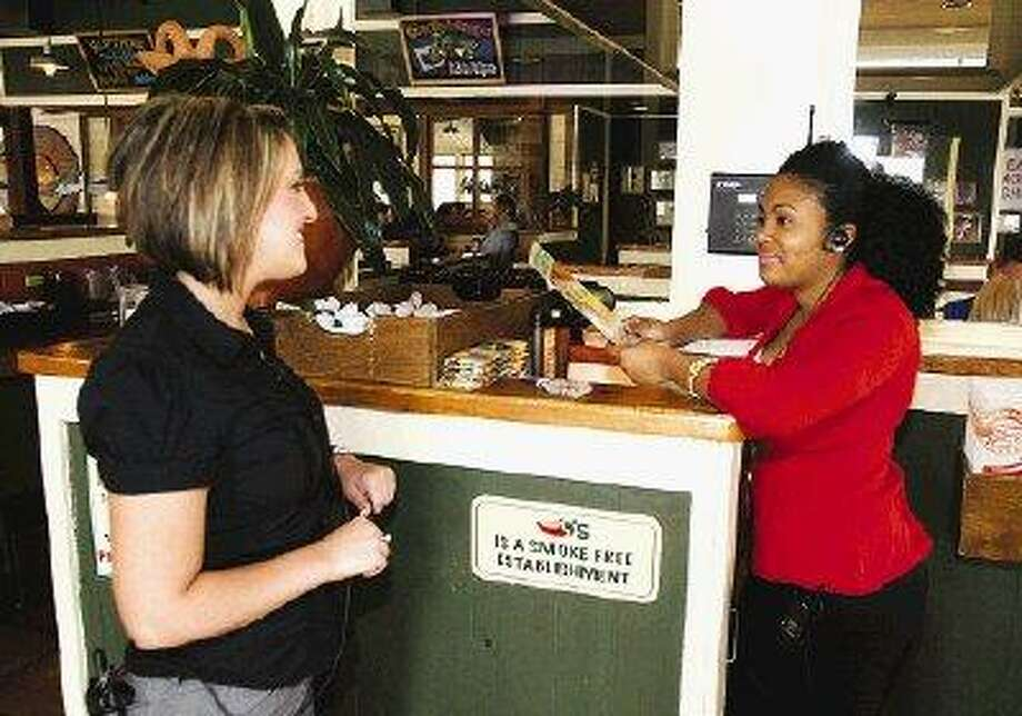 Chili's manager Ashley Dubose, left, said sales were off initially when the restaurant adopted a no-smoking policy Jan. 14 in advance of the Conroe ordinance, but sales have picked back up.