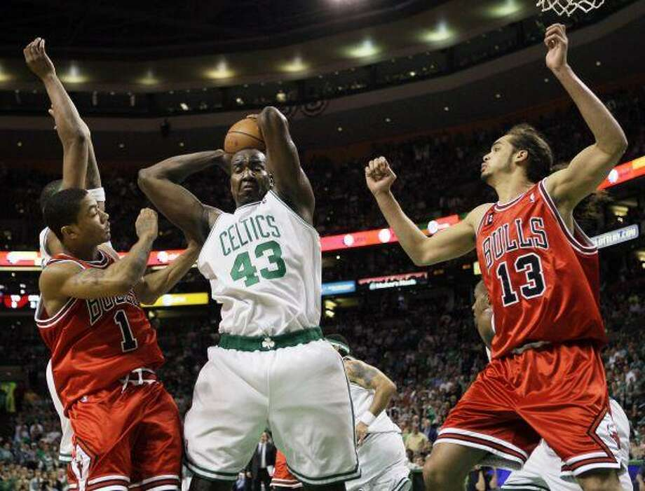 Boston Celtics' Kendrick Perkins (43) pulls down a rebound against the Bulls' Joakim Noah (13) and Derrick Rose (1) during the second quarter of Game 7 Saturday in Boston. / AP