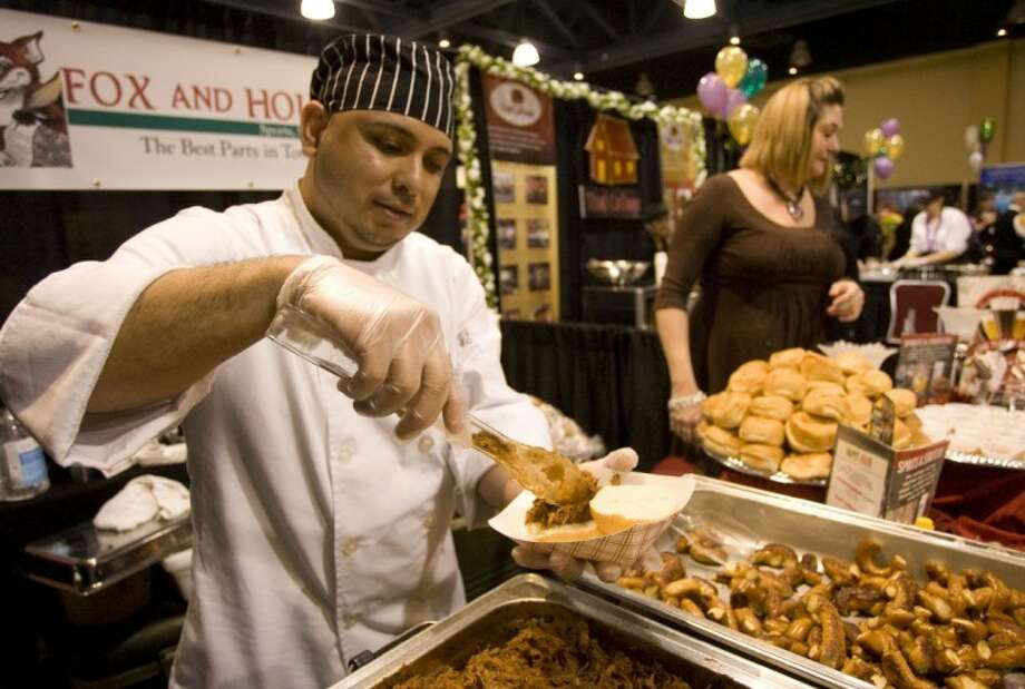 Victor Barrega prepares sliders for visitors at the Fox and Hound Pub & Grill booth at the 26th Annual Taste of the Town on Thursday in The Woodlands. Photo: Staff Photo By Eric S. Swist