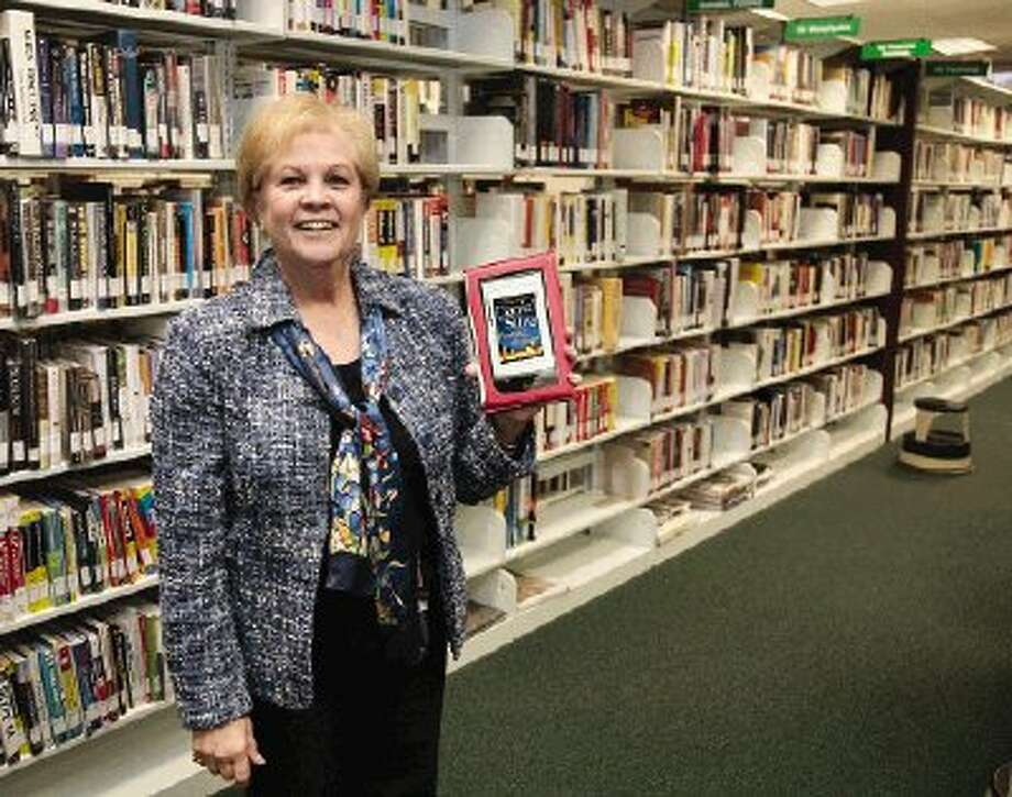 E-readers, like the one held by Jerilynn Williams, director of the Montgomery County Memorial Library System, can hold thousands of books and are increasingly popular with the public.