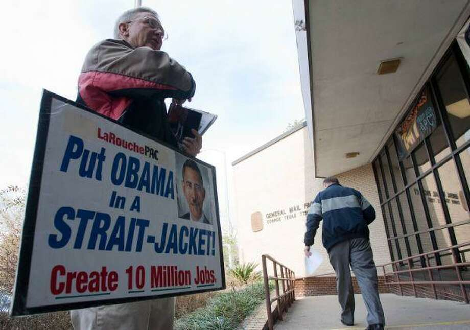 John Jambor distributes fliers as he protests the Obama presidency Wednesday outside the United States Post Office in Conroe. / The Courier