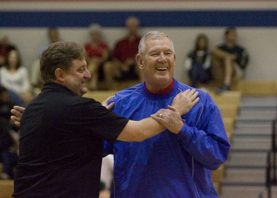 Oak Ridge High School basketball coach, Rob Stewart, left, embraces 1986-87 Oak Ridge High School district championship basketball coach Bob Deegan during a half-time ceremony Friday honoring the 25th year anniversary of the team. Photo: Staff Photo By Eric S. Swist