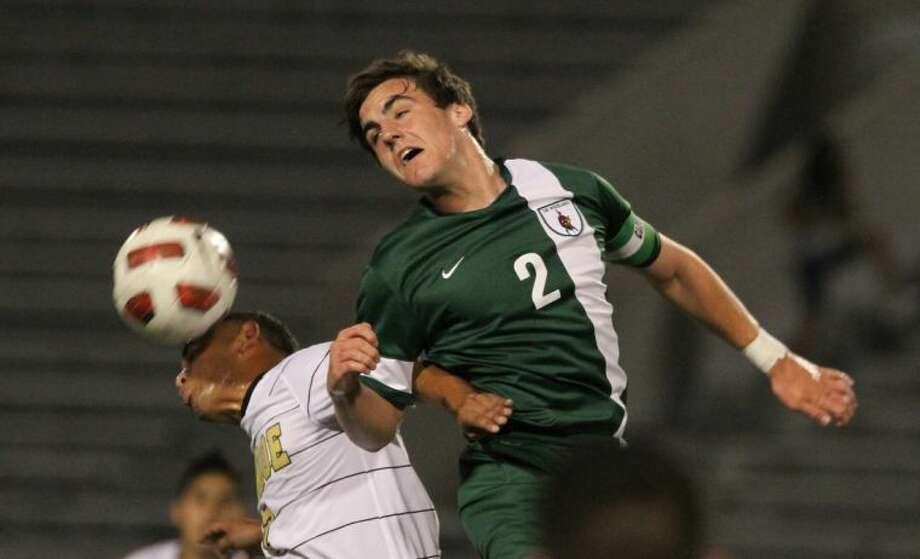The Woodlands midfielder Vince Miller heads the ball past Conroe midfielder Jose Luis Sanchez during Tuesday night's match. To view or purchase this photo and others like it, visit HCNpics.com. Photo: Jason Fochtman
