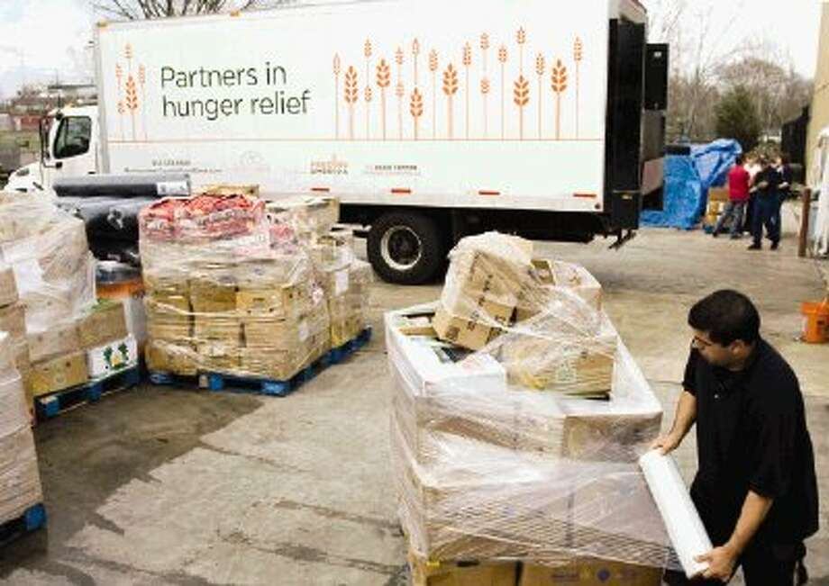 Michael Sandoval wraps a pallet of food as the Montgomery County Food Bank's newest commercial truck is seen in the background Friday in Conroe. Photo: Staff Photo By Eric S. Swist