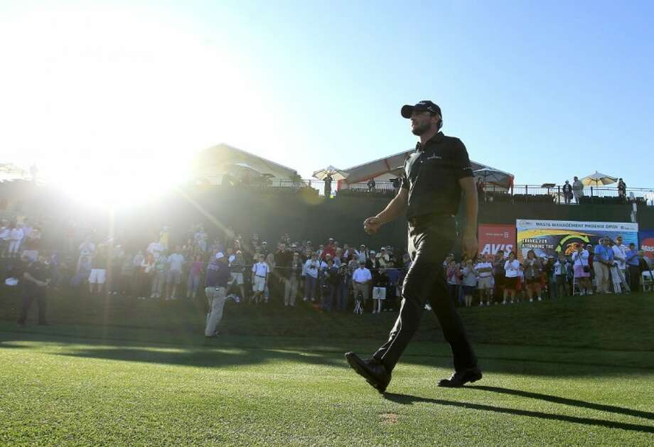 Kyle Stanley walks back onto the 18th green after winning the Phoenix Open golf tournament Sunday in Scottsdale, Ariz. Stanley came from behind to win the tournament, scoring a final round 65, for a tournament total of 15-under par. Photo: Ross D. Franklin