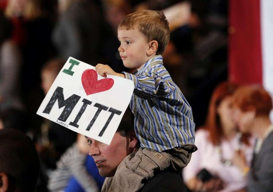 Tommy Sholeff, 3, holds a sign as he sits on the shoulders of his father Jim Sholeff, at the Nevada caucus night victory celebration for Republican presidential candidate, former Massachusetts Gov. Mitt Romney in Las Vegas, Saturday, Feb. 4, 2012. (AP Photo/Gerald Herbert) Photo: Gerald Herbert