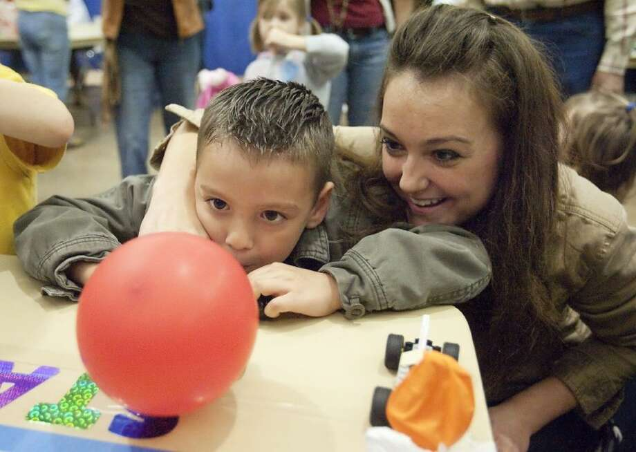 Corne Garcia helps her son, Anthony, blow up a balloon to propel a car at the the SCI://TECH Expo at the Lone Star Convention Center on Saturday. See more photos online at www.yourconroenews.com/photos. Photo: Karl Anderson