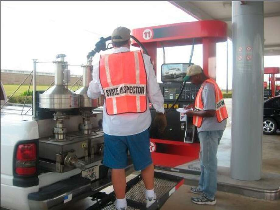 Inspectors from the Texas Department of Agriculture check the calibration on this Texaco Station pump, operated by Woodlands-based Petroleum Wholesale L.P. Inspectors found that 985 of the 1,700 Petroleum Wholesale pumps inspected in Texas were dispensing less than a full gallon of gas or diesel fuel.
