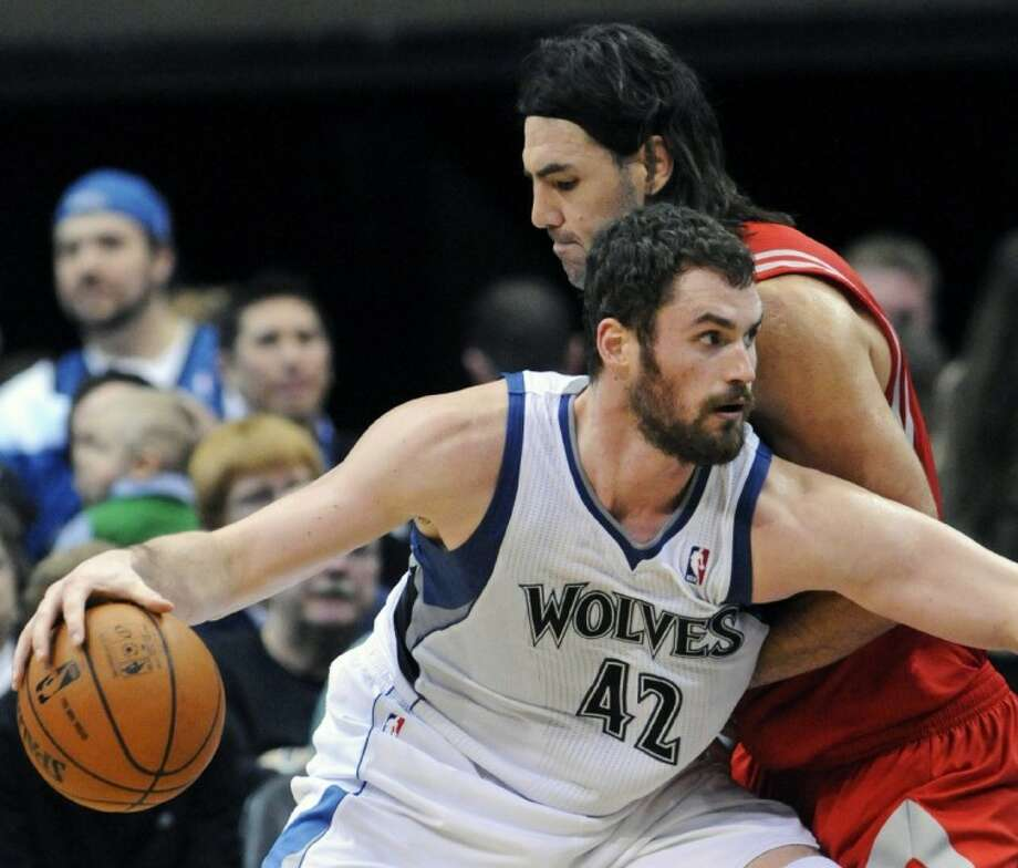 "FILE-This Feb. 4, 2012, file photo shows Minnesota Timberwolves' Kevin Love driving around Houston Rockets' Luis Scola in the second half in Minneapolis. Love, his team's leading scorer and rebounder, was suspended for two games by the NBA Monday for ""driving his foot into the upper body and face of Scola as Scola was lying on the floor."" Photo: Jim Mone"