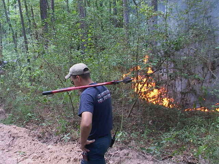 Firefighters battle an out-of-control burn near FM 1314 Thursday afternoon. Near-drought conditions and ill-advised outdoor burns have force county firefighters to battle approximately five to 10 wildfires a day recently.