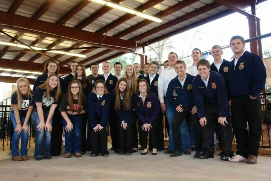 FFA students from The Woodlands High School and The Woodlands College Park High School pose at the new pig barn, located off of Pruitt Road, which was rebuilt over the last year after a tragic fire which killed 17 pigs on Feb. 1, 2011.