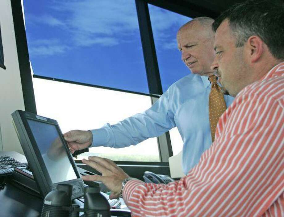 Lone Star Executive Airport air traffic controller Mark Wester, right, describes the function of various controls to Congressman Kevin Brady, R-The Woodlands, following the tower's dedication ceremony in Conroe Tuesday. / The Courier