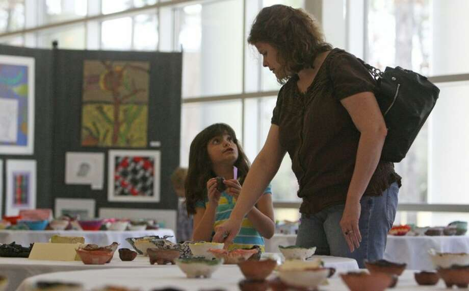 Karen Amador and daughter Olivia look at handmade bowls available during the John Cooper School National Art Honor Society's annual Empty Bowls Project held at the school Feb. 19. The project aims to raise money for hunger relief in the community.