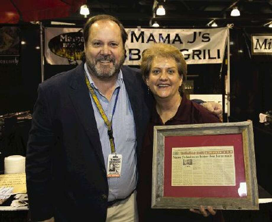 Martha Janousek, founder of Mama J's Barbecue, located at 3091 College Park, welcomes Houston Community Newspaper restaurant reviewer Brad Meyer to her booth at the annual Taste of The Woodlands on Thursday where she had his original review of the restaurant framed and on display for the public.