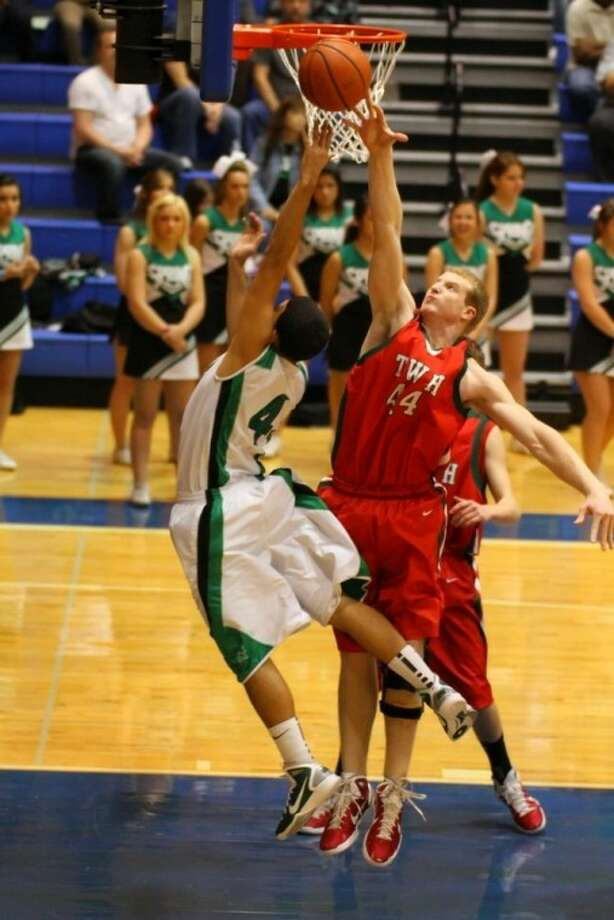 The Woodlands senior center Brian Nordstrom defends a layup against Spring's Eddie Miller during Tuesday night's Region II-5A bi-district victory.