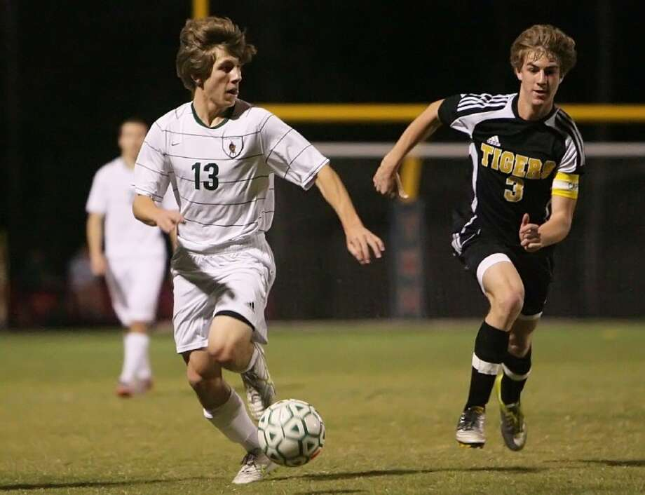 The Woodlands forward Tyler Karr dribbles downfield against a Conroe defender during Tuesday night's game.