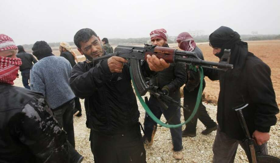 A member of the Free Syrian Army aims during weapons training outside Idlib, Syria, Tuesday. Photo: STR