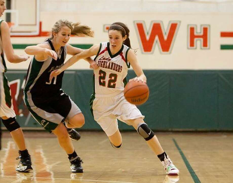 Sophomore point guard Paige Bradley dribbles downcourt against a Kingwood Park defender during Friday's game at The Woodlands High School. / The Courier