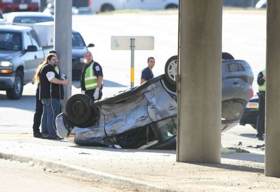 Emergency personnel work the scene of a two-vehicle accident at Loop 336 under the Interstate 45 overpass Wednesday in Conroe. Photo: Jason Fochtman