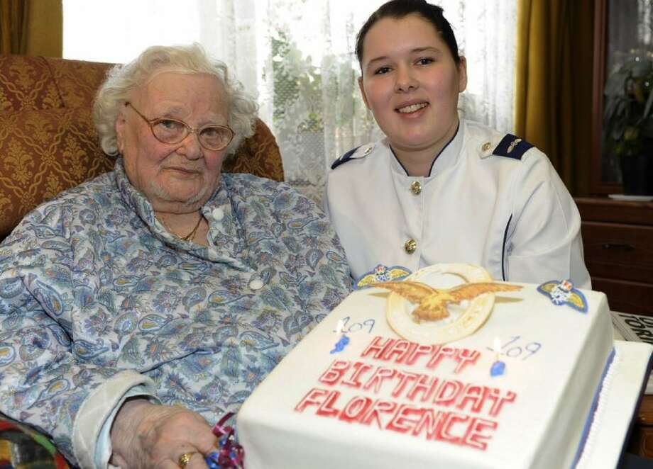 In this Feb. 19, 2010 photo released by the British Ministry of Defense shows Florence Green, left, on her 109th birthday being presented with a birthday cake by LAC Hannah Shaw on behalf of the RAF at her home in King's Lynn, east England. Photo: Sac Chris Hill/MoD