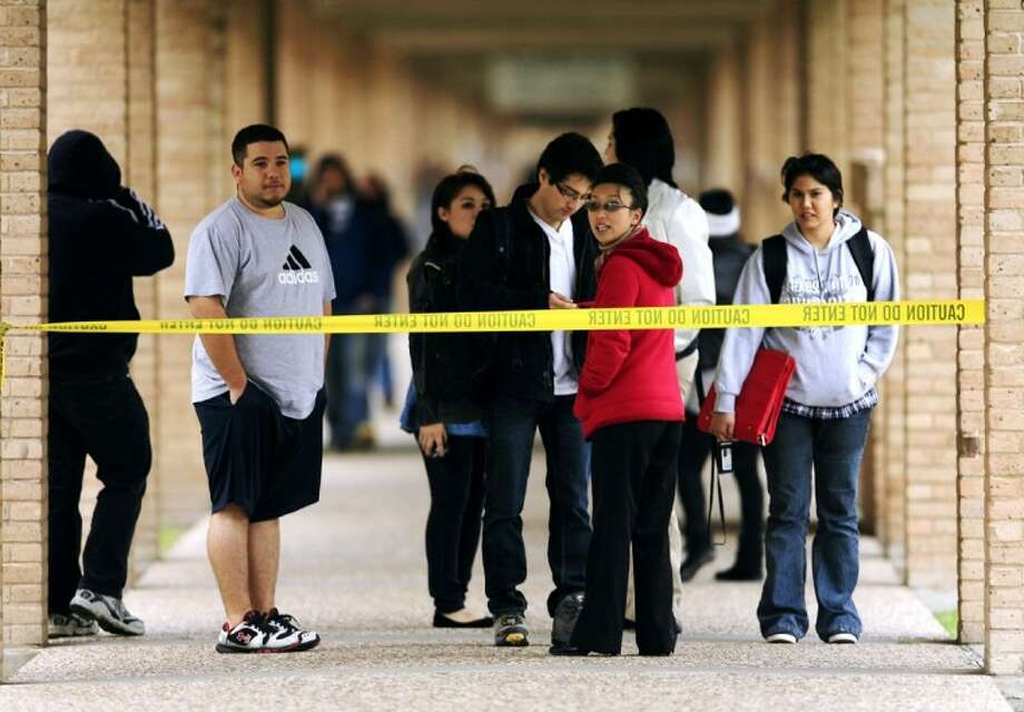Students watch as police investigate the scene where a woman's body was discovered at the Science Building Monday on the University of Texas-Pan American campus in Edinburg. Police are looking into the possibility of whether the female fell to her death from the third floor near an outdoor stairwell. Photo: Gabe Hernandez