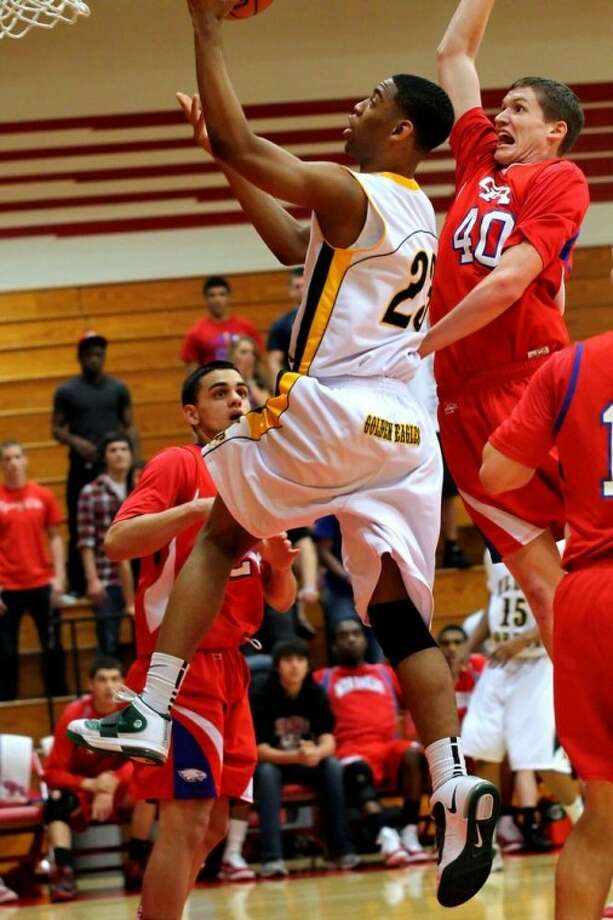Klein Forest's Jacoby Green goes up for a layup as Oak Ridge's Taw Mann closes in during Tuesday night's Region II-5A bi-district game at Tomball High School.