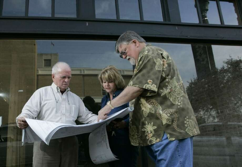 Contractor Joe Fleshner reviews blueprints for the new Texian restaurant with Ruth and Jay Ross Martin outside the planned site of the establishment in downtown Conroe.
