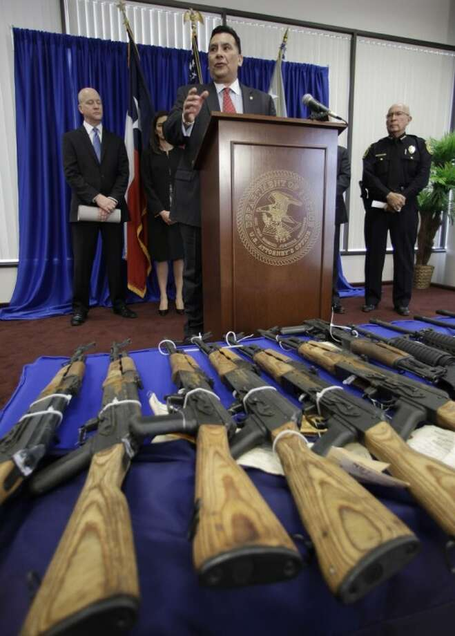 Seized firearms destined for the Los Zetas drug trafficking organization in Mexico are seen in front on Assistant Special Agent in Charge Crisanto Perez, Bureau of Alcohol, Tobacco, Firearms and Explosives, at a news conference Wednesday in San Antonio. The U.S. Attorney's office announced two San Antonio men have been sentenced to federal prison for their roles in firearms straw purchasing and trafficking. Photo: Eric Gay