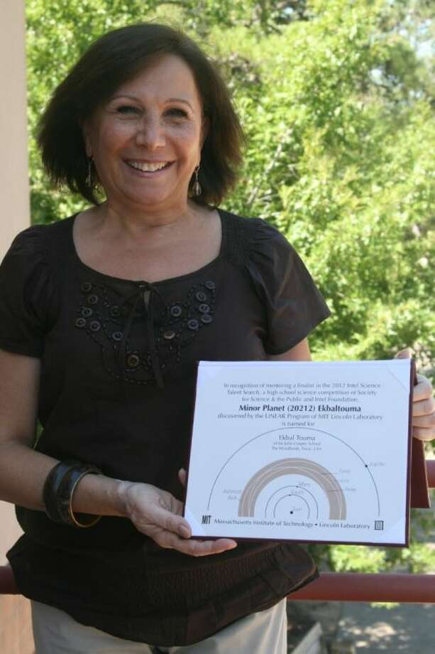 Ekbal Touma, a seventh-grade science teacher at John Cooper School, holds a leather-bound certificate celebrating the naming of a minor planet after her by the Massachusetts Institute of Technology (MIT) Lincoln Laboratory. Touma received the honor in recognition of mentoring Oliver Quintero, a former student and finalist in the Intel Science Talent Search.