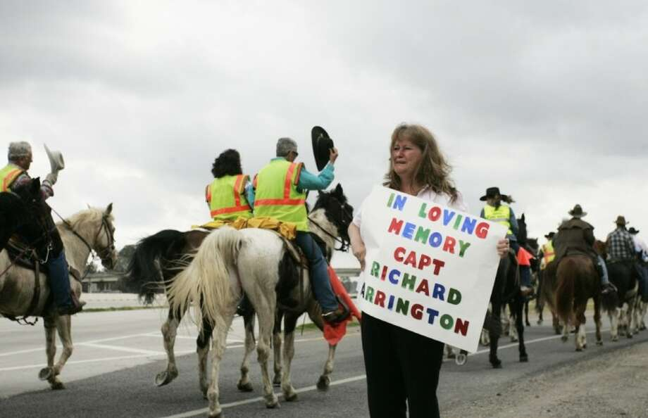 Marsha Edwards, a criminal court coordinator and auditor with Precinct 4 Justice of the Peace Office, holds a sign in memory of her father Capt. Richard Arrington as members of the Old Spanish Trail Ride make their way down the US 59 frontage road last Thursday morning. Arrington, who served with the Harris County Precinct 3 Constable's Office, led the trail ride in his patrol car since the early 1980s.