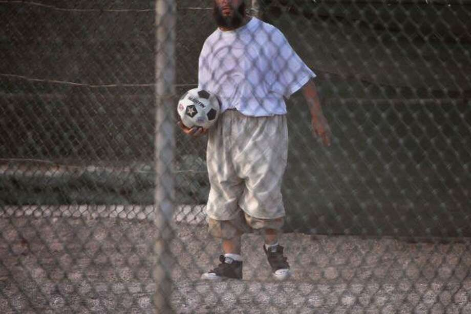 A Guantanamo detainee holds a soccer ball inside the exercise yard at Camp 4 detention facility, at Guantanamo Bay U.S. Naval Base, Cuba. President Barack Obama will restart military tribunals for a small number of Guantanamo detainees, reviving a Bush-era trial system he once assailed as flawed, but with new legal protections for terror suspects, U.S. officials said. The changes are to affect the small portion of Guantanamo detainees who face charges, according to officials. / AP